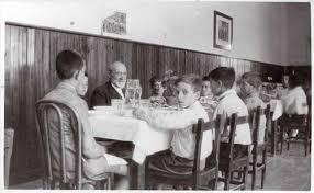 Imagen del maestro con un grupo de alumnos en un comedor