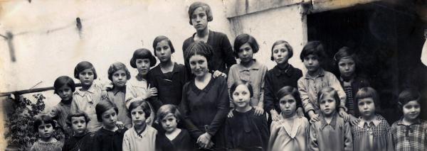 Foto antigua de una maestra con sus alumnos/as